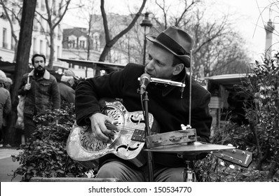 PARIS - MARCH 10: Blues-rock guitarist Rene Miller playing his Dobro guitar at street market on March 10, 2013 in Paris, France.