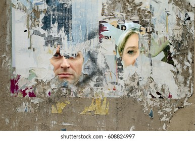 Paris. March 26, 2017 - French elections 2017: Wall with scratched pictures of Emmanuel Macron and Marine Lepen.