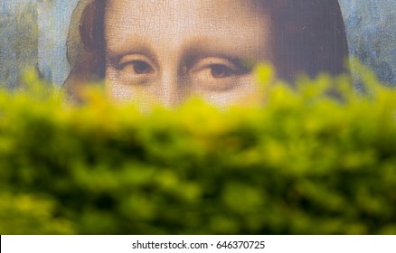 PARIS - MAY 07: Mona Lisa's look behind of the bushes, a large billboard in the garden of Tuileries Garden on May 07. 2017 in Paris