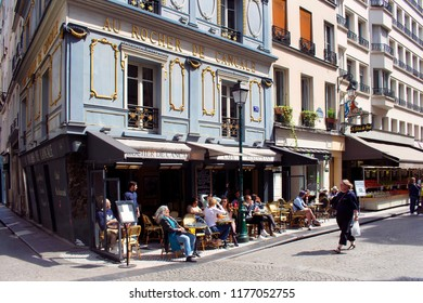 PARIS - MAY 18, 2018: People enjoy sunny weather at a traditional bistro  cafe on one of famous streets (Rue Montorgueil) in Paris. Woman passes by.