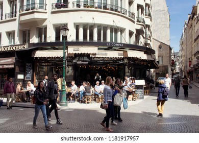 PARIS - MAY 18, 2018: People walk on famous Rue Montorgueil street in Paris. A traditional cafe / bistro place is also in the view.