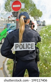 PARIS - MAY 20, 2014 - A french police woman control car speed with a mobile radar