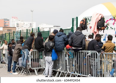 PARIS - MAY 5, 2017: A group of migrants wait to enter the humanitarian centre for refugees in northern Paris.