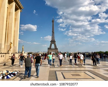 PARIS - MAY 8, 2018: Tourists and souvenir sellers near the Eiffel Tower on the Esplanade du Trocadéro in Paris, France.
