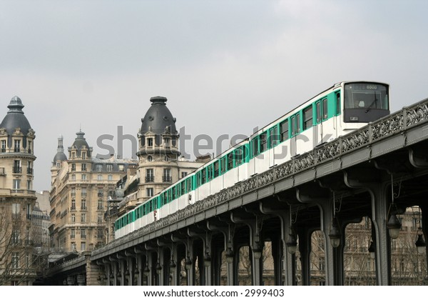 paris metro train on a bridge emerging from in-between two close buildings