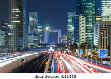 Paris night cityscape with modern buildings in business district La Defense with dynamic street traffic and car lights. Glass facade skyscrapers. Concept of economics, finances. Copy space. Toned