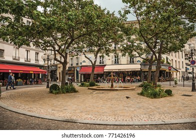 """Paris, northern France - July 12, 2017. Small square with fountain, trees and restaurants in the middle of the """"Quartier Latin"""" in Paris. Known as one of the most impressive world's cultural center."""