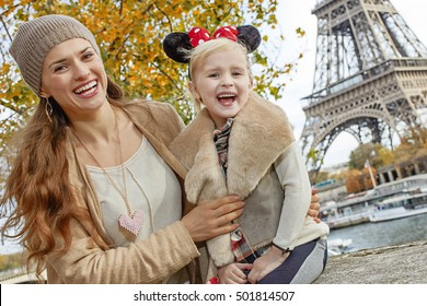 PARIS - November, 11, 2015: Portrait of smiling tourists mother and daughter in Minnie Mouse Ears on embankment in Paris, France sitting on the parapet