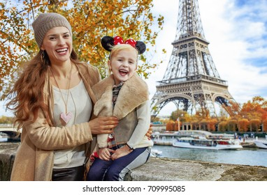 PARIS - November, 11, 2015: Portrait of smiling tourists mother and daughter in Minnie Mouse Ears on embankment near Eiffel tower in Paris, France sitting on the parapet