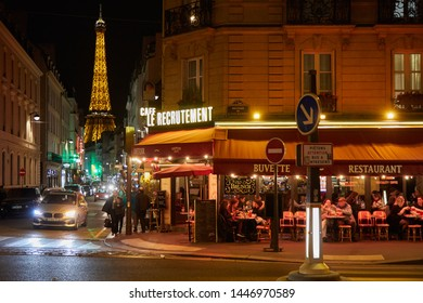 PARIS - NOVEMBER 8, 2018: Eiffel tower illuminated at night and street with people and typical restaurant in Paris, France
