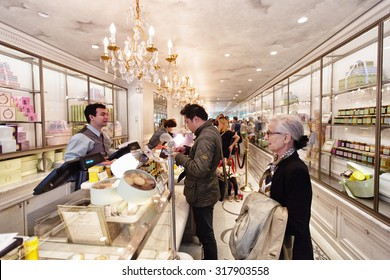 PARIS - OCTOBER 14, 2014: Shoppers at the famous Laduree bakery and tea room in Paris. Laduree was founded in 1862 and is a luxury brand known for its macaroon cookies in many flavors and colors.