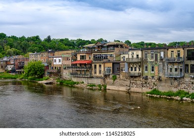 """Paris, Ontario, Canada - June 09, 2018: Restaurants and houses on the Grand River in Paris. The town was established in 1850 was voted """"the Prettiest Little Town in Canada"""" by Harrowsmith Magazine."""