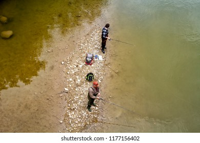 Paris, Ontario, Canada - June 9, 2018: Man Fishing in a shallow water river in Paris, Ontario.
