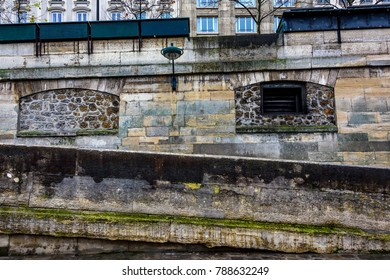 Paris Seine river walkway showcasing green moss covered ancient walls and street lamps.