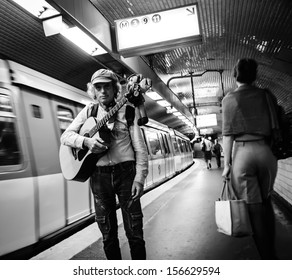 PARIS - SEPT 22: Musician with guitar and funny toy in Parisian metro as seen on September 22, 2013 in Paris, France. Dozens buskers perform on the streets and in the metro of Paris.
