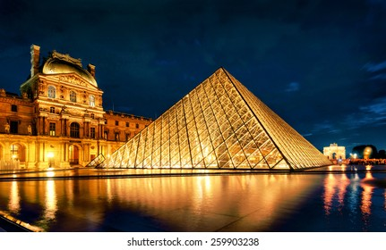 PARIS - SEPT 25, 2013: Louvre museum at night, France. Louvre is one of the main tourist attractions in Paris. Illuminated Louvre and modern pyramid. Evening view of Louvre with reflections in water.