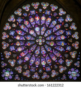 PARIS - SEPT 25, 2013: Rose stained glass window of Notre Dame Cathedral, inside view. South Rose window with a diameter of 12.9 meters. Medieval colorful rose window closeup. Nice scenery indoor.