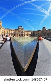 PARIS - SEPT 8: The world-famous entrance to the Louvre - fountain September 8, 2012 in Paris. Tourists resting on a granite fence fountain. Picture taken Fisheye lens