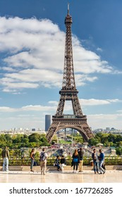 PARIS - SEPTEMBER 20, 2013: Tourists walk on a viewing platform in front of the Eiffel Tower or Tour Eiffel in summer, France. Eiffel Tower over the street. Scenic view of Eiffel Tower.