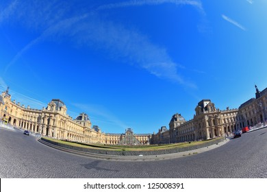 Paris, September 8: The world-famous Louvre - September 8, 2012 in Paris. Tourists take pictures of the glass pyramid entrance. Traces in the sky jet. Picture taken Fisheye lens