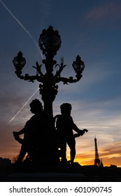 Paris skyline at sunset, with statue silhouettes, as seen from the Pont Alexandre III bridge, Paris, France