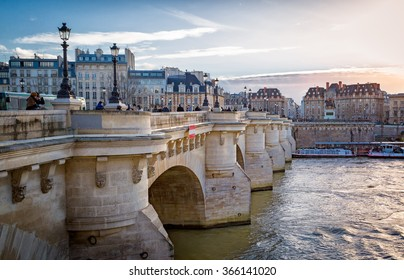 Paris sunset lights up a bridge and buildings along the Seine