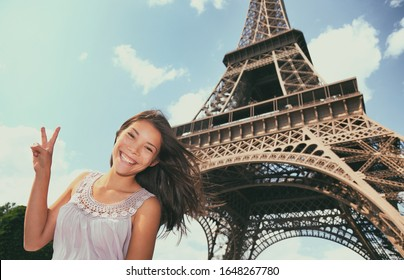 Paris tourist woman at Eiffel tower, France, Europe summer vacation. Asian girl doing V sign posing in front of famous french landmark.