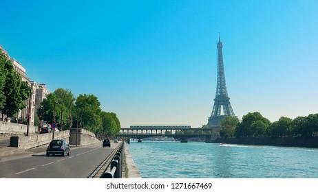 Paris traffic with view of Eiffel Tower and metro train on Bir-Hakeim metal bridge in the morning