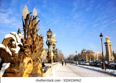 Paris under snow. View of Alexandre III Bridge. Grand Palais and Petit Palais buildings at background.
