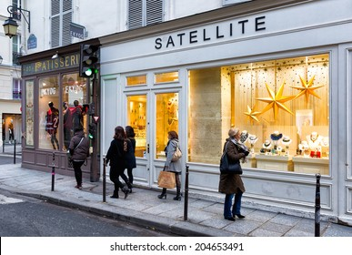 PARIS-DEC 23, 2013: Holiday shoppers on a Paris street in the Marais, the historic district in the heart of the city, with store windows dressed up for Christmas.