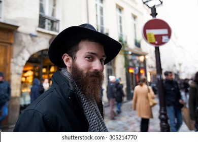 PARIS-DEC 31, 2013: Rue des Rosiers in the Jewish district of the historic Le Marais neighborhood. An unidentified man in the foreground wears a type of black hat worn by orthodox Jews.