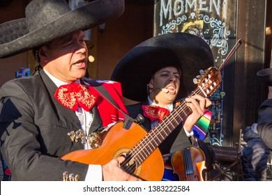 Paris/France - 10 25 2018: Street group of Latin mariachi musicians playing national traditional Spanish and Mexican music. Guitar player and violinist. Street performance, street musicians.