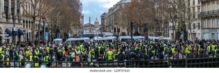 "Paris/France -11.24.2018 Protest ""'Yellow Vests"" (Gilets Jaunes) against the government of Emanuel Macron Place de La Madeleine.  The crowd at the protest"