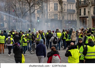 "Paris/France -11.24.2018 Protest ""'Yellow Vests"" (Gilets Jaunes) against the government of Emanuel Macron Place de La Madeleine.  Moments after police retaliation with tear gas and smoke bombs"