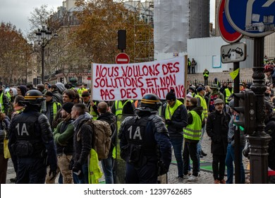"Paris/France -11.24.2018 Protest ""'Yellow Vests"" (Gilets Jaunes) against the government of Emanuel Macron Place de La Madeleine.  Signs, banners, satire"