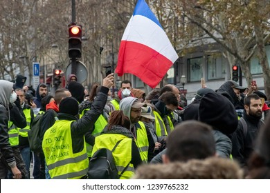 """Paris/France -11.24.2018 Protest """"'Yellow Vests"""" (Gilets Jaunes) against the government of Emanuel Macron Place de La Madeleine.  Protesters and gendarmes"""