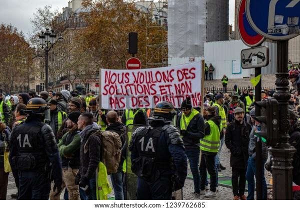 """Paris/France -11.24.2018 Protest """"'Yellow Vests"""" (Gilets Jaunes) against the government of Emanuel Macron Place de La Madeleine.  Signs, banners, satire"""