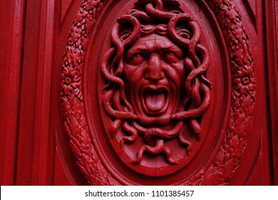 Paris/France - April 10 2018: Exterior design, red door with woodcarving of Medusa Gorgon's head. Greek antique character in the red color. Taken in the old quartalof Paris.