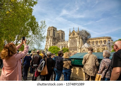 Paris,France - April 18, 2019: Unidentified people on the Seine riverside are looking to the remains of Notre Dame Cathedral two days after a big fire partially destroyed the famous Parisian landmark.