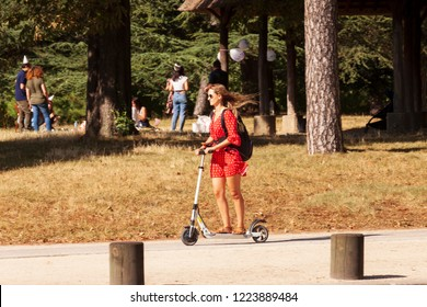 PARIS/FRANCE - JULY, 28, 2018: Woman in red dress travels in the city with electric scooter. Park Bois de Boulogne.