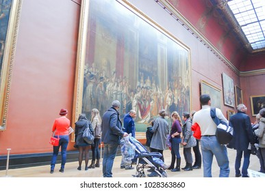 Paris-France -March 5,2014: Non focus ,many tourists   inside big hall at Louvre's museum the most big collection place and looking famous painting of historic in France background red-pink wall .