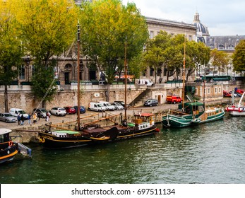 PARIS/FRANCE - OCTOBER 20, 2016: Tourists waits to go aboard house boats, transformed into restaurants and coffee shops, that are docked in the Seine river.