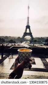 PARIS/FRANCE - OCTOBER 2019 : Coffe cup in hand with Eiffel Tower in background