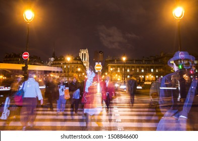 PARIS,FRANCE-NOV.16,2009:  people crossing the street near the louvre in paris, second curtain flash sync technique used to create ghosting effect