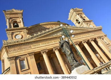 The Parish Church of Santa Maria in Mosta, Malta. Rotated view of the Parish Church of Santa Maria in Mosta, Malta with bronze statue of Virgin Mary and street lamp topped by a cross.