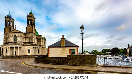 The parish church of Ss. Peter and Paul and with their green domes, the bridge with the river Shannon in Athlone town, wonderful cloudy day in the county of Westmeath, Ireland