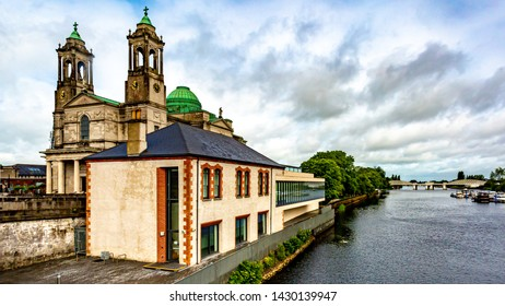The parish church of Ss. Peter and Paul with their green domes beside the river Shannon in Athlone town, wonderful cloudy day in the county of Westmeath, Ireland