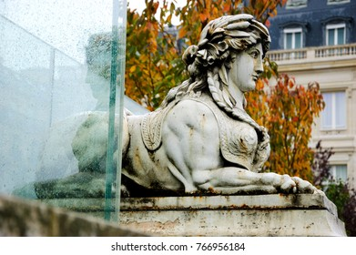 Parisian autumnal mystery. Sphinx and its reflection in wet glass after rain.