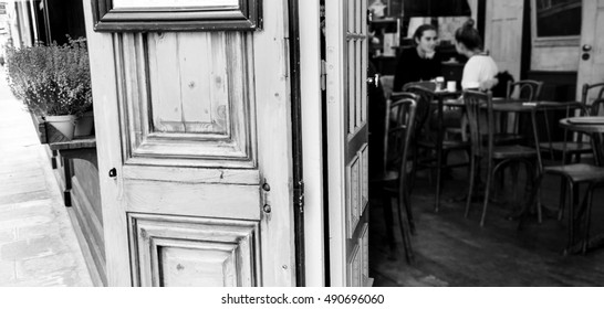 Parisian cafe. Blurred interior with young couple. Romantic Paris concept. Black and white.