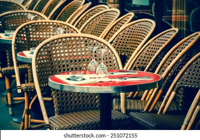 Parisian cafe terrace. Selective focus on the glasses. Aged photo.